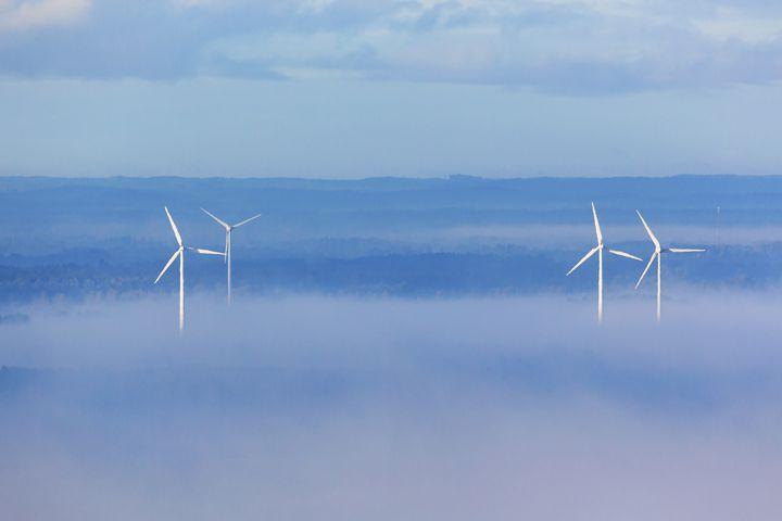 Wind powers in misty countryside landscape
